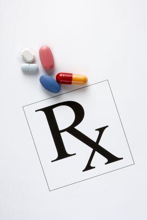 dosaggio: Pillole, capsule e Rx simbolo girato su sfondo bianco con ombre morbide