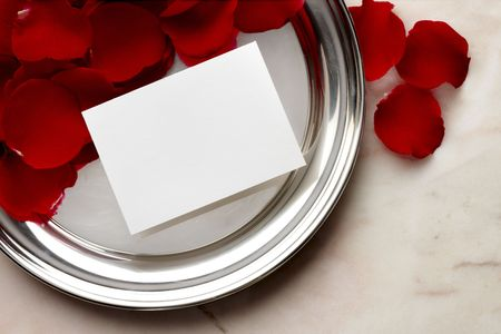 Silver tray, red rose petals, blank white card shot on marble