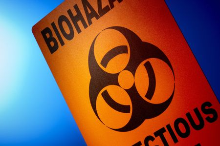 substances: Orange biohazard sign dramatically shot in front of glowing blue background Stock Photo