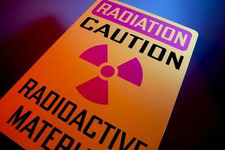 hazardous waste: Orange radiation sign shot at dramatic angle with glowing background Stock Photo