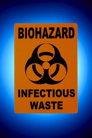 substances: Orange biohazard sign shot in front of glowing blue background Stock Photo