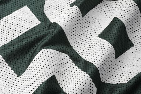 Close up shot of green textured football jersey with partial number photo