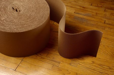 Roll of corrugated packing material uncurling on wooden floor photo