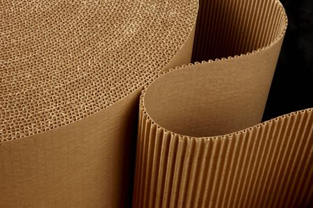 close up shot of corrugated packing material uncurling on black background photo