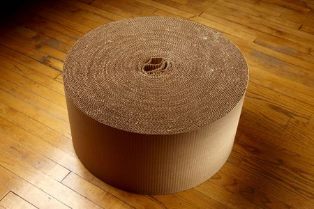 Roll of corrugated packing material shot on wood floor photo