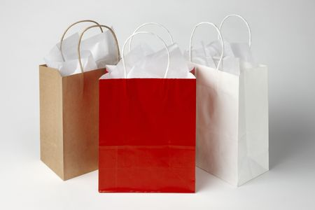 shoppings: 3 shoppings bags with tissue paper shot on soft white background with room for copy Stock Photo