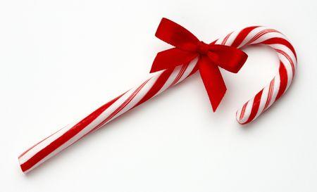 Candy cane met rode strik geschoten op witte achtergrond met zachte schaduw