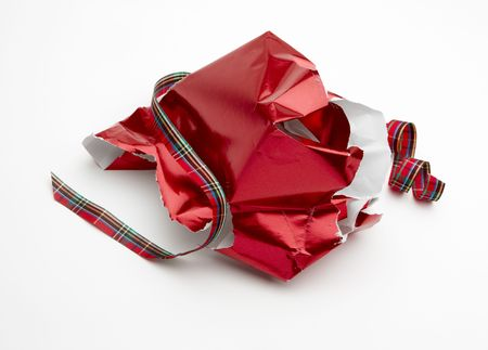 torn: torn Christmas gift wrapper and ribbon shot on white background with soft shadow and room for copy Stock Photo