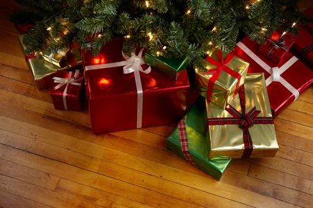 xmas background: Wrapped gifts under a Christmas tree with room for copy Stock Photo