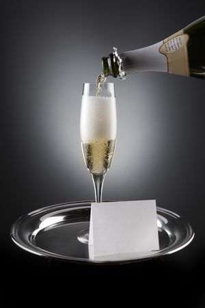space for type: Champagne pours into flute sitting on silver tray with white place card including space for type