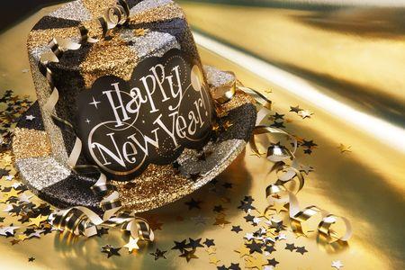 De hoed van het nieuwe jaar van Glittery met slingers en confettien op gouden metaalachtergrond wordt geschoten die Stockfoto