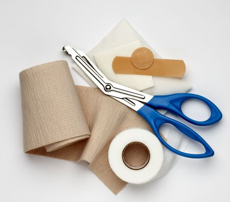 Gauze, ace bandage, tape, scissors and bandages shot on white background with a soft shadow