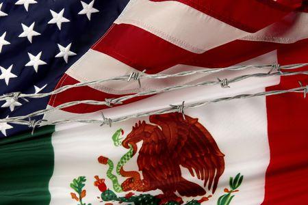 bandera mexicana: Close-up disparo de M�xico y de Estados Unidos banderas separados por alambre de espino