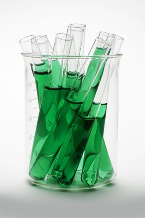 Glass scientific flask contains several test tubes of green chlorophyll extract shot on white background with soft shadow photo