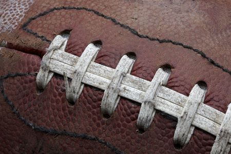 pigskin: Close-up shot of old roughed up football fills frame Stock Photo