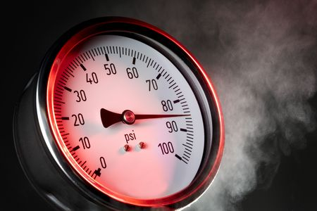 gauges: pressure gauge under extreme stress with steam and red warning light Stock Photo