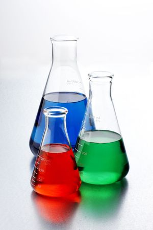 three flasks of colorful chemicals shot on textured metal lab table Stock Photo