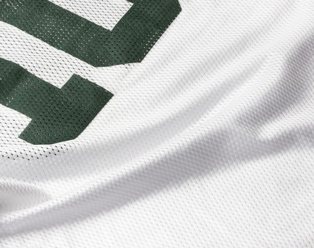 Close up shot of white football jersey with cropped green number
