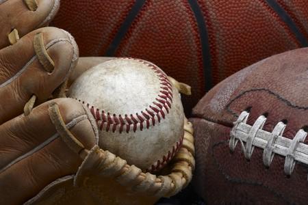 close up shot of well worn baseball in baseball glove, football and basketball Archivio Fotografico