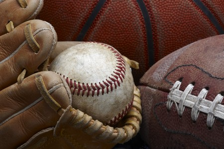 close up shot of well worn baseball in baseball glove, football and basketball Stock Photo