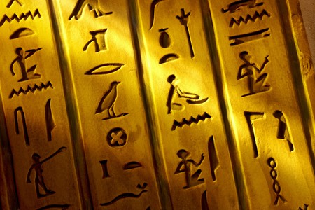 Close up shot of Egyptian hieroglyphics carved into stone with shaft of light Imagens