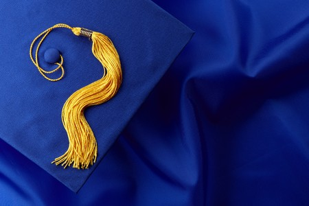 gown: Blue mortarboard and yellow tassel shot on blue graduation gown, space for copy