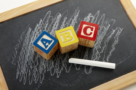 abc's: Alphabet blocks shot on black chalkboard with white chalk scribbles