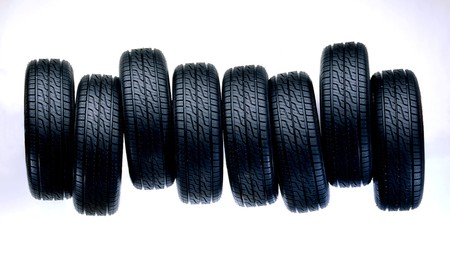 tire: Row of eight new auto tires with treads facing camera lens and space for copy