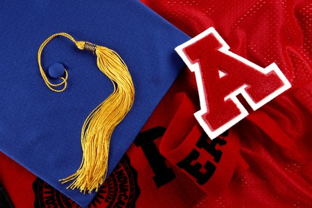 Mortarboard, tassle, pennant and red letter A shot of red textured material