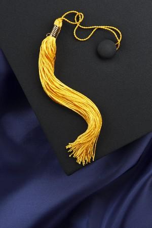 黄色タッセル付き黒鏝板ブルー卒業ガウン、コピーのためのスペースで撮影 写真素材