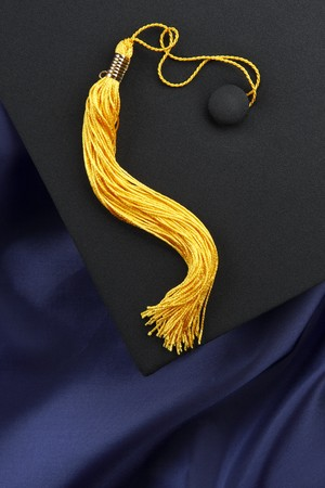 Black mortarboard with yellow tassel shot on blue graduation gown, space for copy