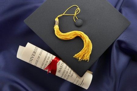 cap and gown: Cap, tassel and diploma shot on blue graduation gown