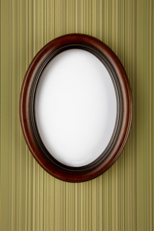 wooden oval picture frame shot on stripped wall paper with space for copy and photograph