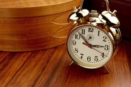 Klassieke alarm klok geschoten op houten tafel met houten mandje en vak, ruimte voor kopie