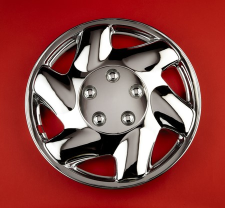 hubcap: Shiny chrome wheel cover shot on red background