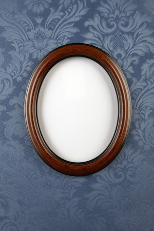 Dark wood oval wall frame shot of vintage blue flocked, floral wallpaper with space for photo to be inserted and room for copy