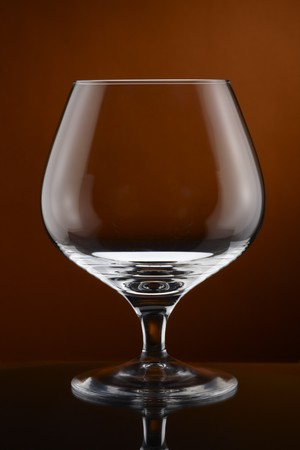 Close up of empty cognac glass shot on rich amber background