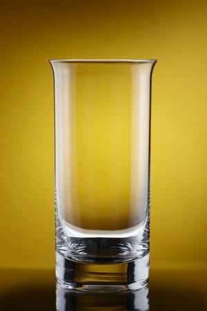 Close up of empty tall glass shot on rich golden background Zdjęcie Seryjne