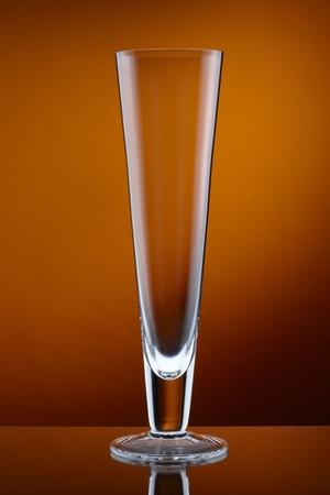 pilsner: close up of empty pilsner glass shot on deep amber background Stock Photo