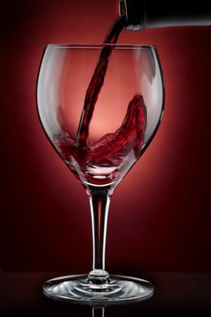 De rode wijn giet van fles in glas, schot op de rijke achtergrond van Bourgondië