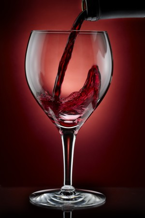 Red wine pours from bottle into glass, shot on rich burgundy background photo