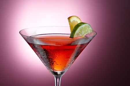 Beautifully lit Cosmopolitan with slices of lemon and lime shot on pink background, space for copy Stock Photo - 7244173