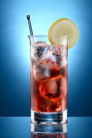 Close up shot of carbonated soda and cranberry juice with ice and slice of lemon shot on blue background Archivio Fotografico