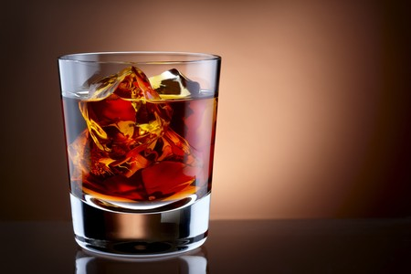 Close up shot of glass filled with whisky and ice, shot on rich background with space for copy