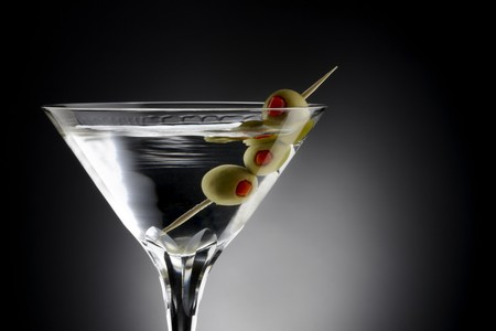 Close up shot of Martini with tooth pick and green olives, shot on black background with space for copy