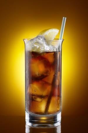 コピーのためのスペースで黄色オレンジ背景にわらショットを飲むとレモンのくさびと冷たいアイスティーの背の高いグラス