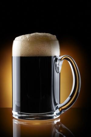 brew beer: Close up disparo de pinta de cerveza oscura dispar� sobre rico fondo marr�n con espacio para copia