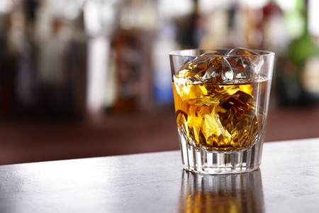 Glass of scotch whisky shot in bar with room for copy