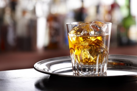 Elegant glass of scotch whisky sitting on silver tray, shot in bar with space for copy