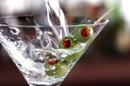 Macro schot van wodka gieten in een martini glas met groene olijven  Stockfoto